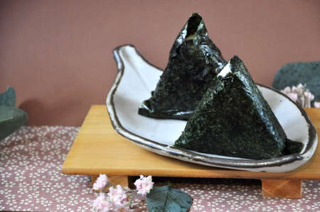 Two pieces of onigiri Japanese food on white plate with copy space on pink background