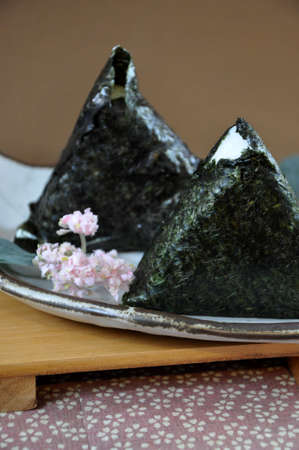 Close up Onigiri Japanese food on plate decorated with little pink  flower