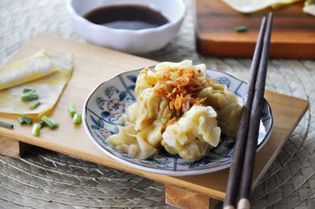 Dish of delicious pork wanton top with fried garlic put on wooden board with chopstick Stock Photo