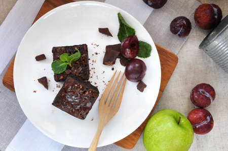 Top view of fudge brownies with fresh plum on white plate