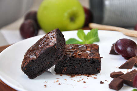 Close up fudge brownie on white plate with fresh fruits on background Stock Photo