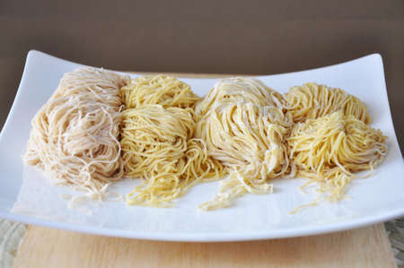 Various kinds of fresh Chinese egg noodles on white plate with copy space on background Stock Photo