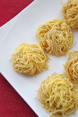 Top view of fresh egg noodles on white plate put on red background