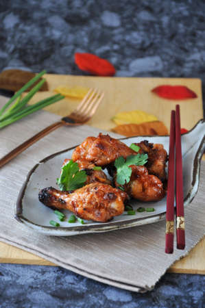 Delicious barbecue chicken drumsticks in Korean style serve on white plate with copy space on background