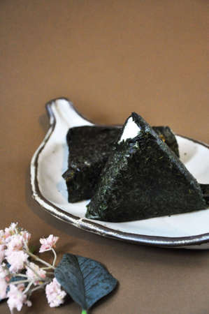 Japanese food Onigiri on white plate put on brown background with space for text