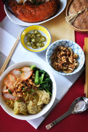 Top view of Chinese food set wanton noodles with grilled pork dish on red background