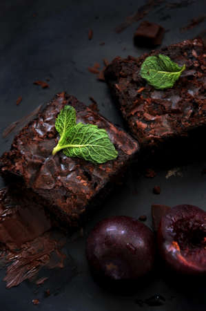 Top view of fudge brownies with fruits on dark background