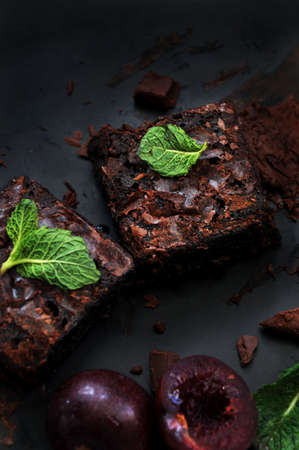 Fudge brownie with messy chocolate on dark background
