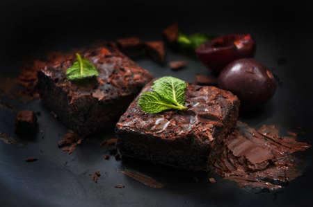 Messy fudge brownies with chocolate and fresh plum on dark background