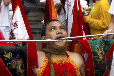 PHUKET, THAILAND - OCTOBER 3 2011: A Mah Song at the Jui Tui Chinese Shrine has his face pierced by two metal rods during a ritual ceremony at the annual Phuket Vegetarian Festival.