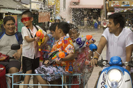 PHUKET, THAILAND - APRIL 13 2013: Father ferries his kids in a moped sidecar as they throw water at people during the Songkran Festival in Phuket.  Editorial