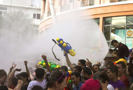 PHUKET, THAILAND APRIL 13: Crowds of revelers are hosed down with water in front of the Jung Ceylon Mall during Songkran in Phuket.
