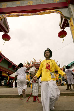 PHUKET, THAILAND - OCTOBER 1 2011: A worshiper in Phuket Town leaves the Jui Tui Chinese Temple after paying homage to the Nine Emperor Gods during the annual Phuket Vegetarian Festival.