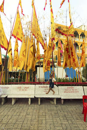 PHUKET, THAILAND SEPTEMBER 30 2011: Under a row of yellow banners at the Jui Tui Chinese Shrine in Phuket Town, a toddler runs across a bench during the annual Phuket Vegetarian Festival. Editorial