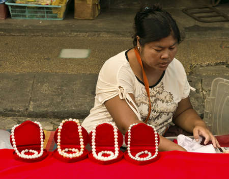 PHUKET, THAILAND SEPTEMBER 30 2011: A female street vendor sells pearl necklaces at the Downtown Market in Phuket Town during the annual Vegetarian Festival.  Editorial