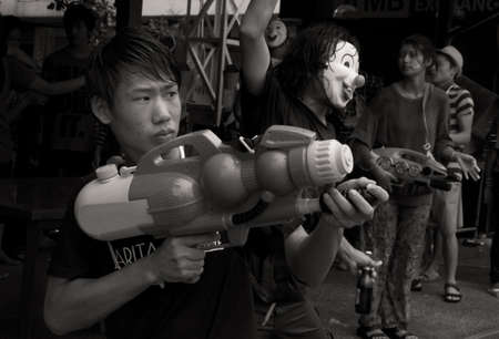 PHUKET, THAILAND - APRIL 13 2013: Revelers celebrate Songkran 2013 by throwing water at pedestrians and motorists alike on Rat-tu-Thit Road in Patong Beach.  Editorial