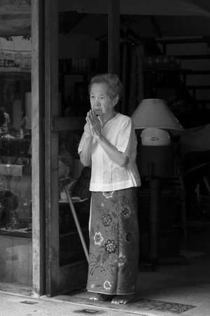 PHUKET, THAILAND - OCTOBER 1 2011: An elderly Chinese Thai woman in PHuket Town clasps her hands in prayer as a street procession move past her at the annual Phuket Vegetarian Festival. Editorial
