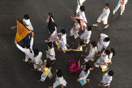 PHUKET, THAILAND - OCTOBER 1 2011: An entourage of attendants accompany two Mah Song (spirit mediums) during a street procession  in Phuket Town during the annual Phuket Vegetarian Festival.  Editorial