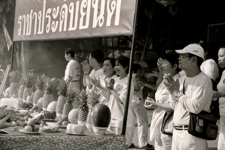 PHUKET, THAILAND - OCTOBER 1 2011: Spectators in ceremonial white stand behind a worship station while watching a street procession in Phuket Town during the annual Phuket Vegetarian Festival.
