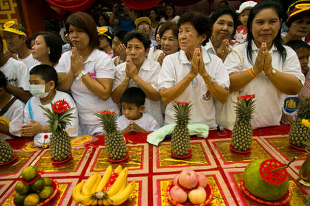 PHUKET, THAILAND - OCTOBER 1 2011: Spectators in ceremonial white stand behind a worship station while they watch a street procession in Phuket Town during the annual Phuket Vegetarian Festival.