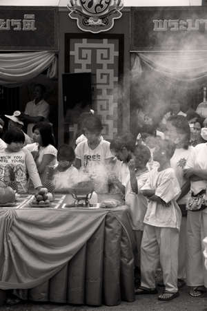 PHUKET, THAILAND - OCTOBER 1 2011: Spectators dressed in ceremonial white in Phuket Town gather around a worship station burning incense during the annual Phuket Vegetarian Festival. Editorial