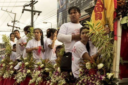 PHUKET, THAILAND - OCTOBER 1 2011: Spectators in ceremonial white ride a float in Phuket Town during the annual Phuket Vegetarian Festival.  Editorial