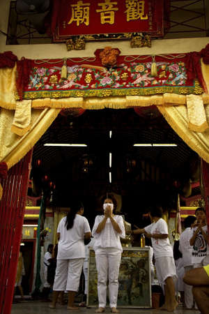 PHUKET, THAILAND - SEPTEMBER 30 2011: A devotee  in ceremonial white garb at the Put Jaw Shrine in Phuket Town  lights incense and offers a prayer to Kuan Yin, Goddess of Mercy during the annual Vegetarian Festival.
