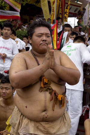 PHUKET, THAILAND - OCTOBER 2 2011: A worshiper clasps his hands in prayer and devotion during the Phuket Vegetarian Festival at the Bang Niew Chinese Shrine in Phuket Town.