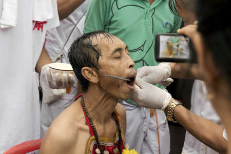 PHUKET, THAILAND - OCTOBER 3 2011: A Ma Song endures the pain of a skewer extraction at the Jui Tui Chinese Shrine in Phuket Town during the annual Phuket Vegetarian Festival.