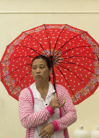 PHUKET, THAILAND - OCTOBER 3 2011: A devotee attending the annual Phuket Vegetarian Festival stands under her umbrella during a rain storm at the Jui Tui Chinese Shrine. Editorial