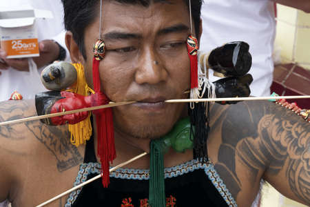 PHUKET, THAILAND - OCTOBER 5 2011: A ma song (vessel of the gods) has his cheeks pierced in a ritual ceremony at the Sui Boon Tong Chinese Shrine during the annual Phuket Vegetarian Festival.