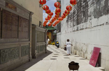 PHUKET, THAILAND - OCTOBER 2 2011:An elderly woman in ceremonial white enters the Shrine of Serene Light Chinese Temple in Phuket Town during the annual Phuket Vegetarian Festival.  Editorial