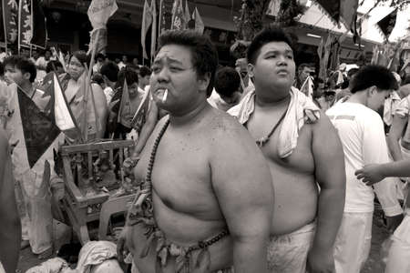 portly: PHUKET, THAILAND OCTOBER 2 2011: Two acolytes return to the Bang Niew Chinese Srhine after the conclusion of a street procession during the annual Phuket Vegetarian Festival.