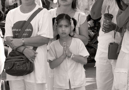 PHUKET, THAILAND OCTOBER 2 2011: A young devotee in Phuket Town clasps her hands in prayer during the annual Phuket Vegetarian Festival.