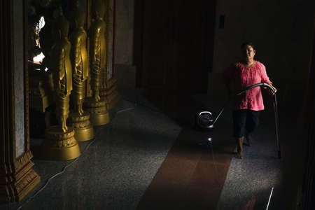 norm: PHUKET, THAILAND APRIL 28 2013: A janitor vacuums the hallway of a building at Chalong Temple in Phuket Town; daily cleaning is the norm due to the large number of visitors.