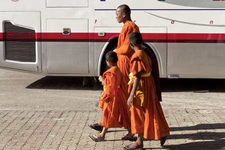PHUKET, THAILAND APRIL 28 2013: A big brother monk looks after two young novices as they tour Wat Chalong, the largest Buddhist temple in Phuket.