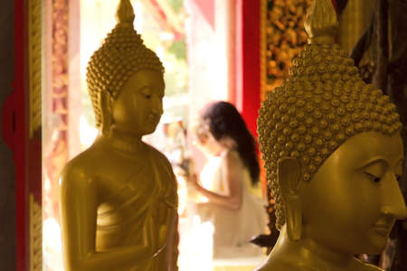 PHUKET, THAILAND APRIL 28 2013: A Thai woman exits a temple building after a Wai Phra offering at Wat Chalong, the largest Buddhist temple in Phuket. Stock Photo - 19599279