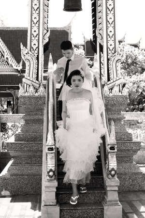concludes: PHUKET, THAILAND APRIL 28 2013: A Thai couple concludes their wedding shoot at Wat Chalong, the largest Buddhist Temple in Phuket and a popular locale for wedding photos among locals.