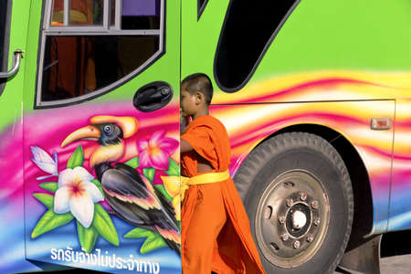 PHUKET, THAILAND APRIL 28 2013: A novice monk boards a tour bus after visiting  Wat Chalong, the largest Buddhist temple in southern island province of Phuket. Stock Photo - 19599278