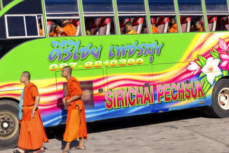 PHUKET, THAILAND APRIL 28 2013: Two monks and a group of Buddhist novices board a tour bus after visiting  Wat Chalong, the largest Buddhist temple in southern island province of Phuket.