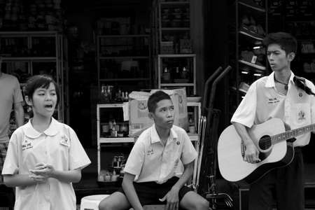 BANGKOK, THAILAND MARCH 18 2012: A trio of Thai student street musicians perform for the crowds at the Chatuchak Weekend Market in Bangkok.