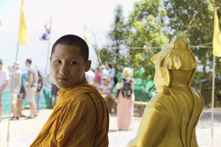 PHUKET, THAILAND FEBRUARY 15 2013: A Buddhist monk visits the Big Buddha Monument, an iconic symbol of Thai Buddhism and one of the most visited religious landmarks in Phuket. Stock Photo - 19639729