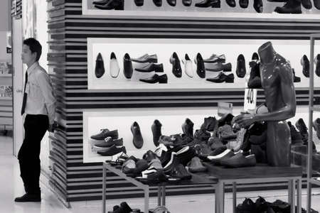 PHUKET, THAILAND MAY 22 2012: A security guard stands watch over shoes in a department store in Patong Beach.