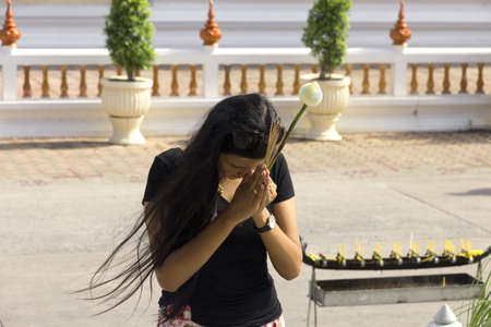 PHUKET, THAILAND MAY 15 2013: A Thai woman holds incense and a flower while offering a prayer at Wat Chalong, the largest Buddhist Temple in Phuket.