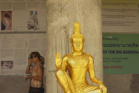 PHUKET, THAILAND FEBRUARY 15 2013: A visitor walks by one of the Little Buddha statues that encircle the base of the Big Buddha monument in Chalong. Stock Photo - 19680279