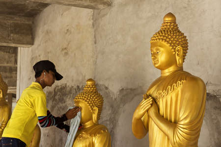 groundskeeper: PHUKET, THAILAND FEBRUARY 15 2013: A groundskeeper at the Big Buddha Statue, an iconic symbol of Thai Buddhism in Phuket, cleans a statue of Buddha at the base of the monument.