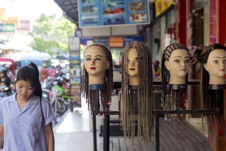 salon beaut�: Phuket Tha�lande 29 JUNE 2012: Une jeune femme marche par une rang�e de bustes de mannequins sur l'affichage ext�rieur d'un salon de beaut� sur Banzaan Road � Patong.