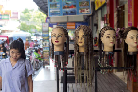 busts: PHUKET THAILAND JUNE 29 2012: A young woman walks by a row of mannequin busts on display outside of a beauty parlor on Banzaan Road in Patong.