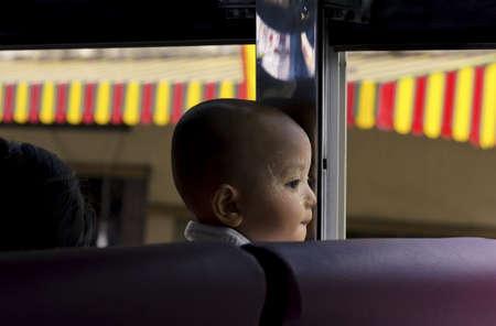 he is public: PHUKET, THAILAND SEPTEMBER 6 2011: A little Burmese boy fresh from his bath (talcum powder on  face) gazes out an open window as he rides a public bus through Phuket Town.