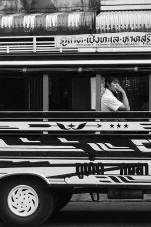 PHUKET TOWN, PHUKET, THAILAND AUGUST 12 2012: A young student waits for departure at a bus depot in downtown Phuket Town.